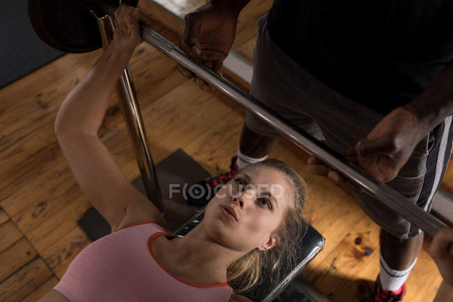 Young female boxer exercising with barbell in fitness studio — Stock Photo