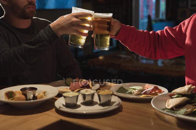 Close-up of friends toasting beer glasses in pub — Stock Photo