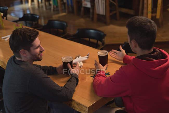 Amigos a falar uns com os outros enquanto beber cerveja no balcão no pub — Fotografia de Stock