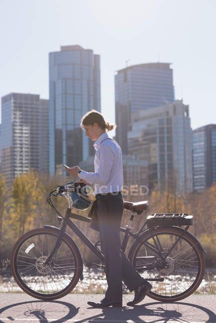 Человек с помощью мобильного телефона во время прогулки на велосипеде по дороге в городе — стоковое фото