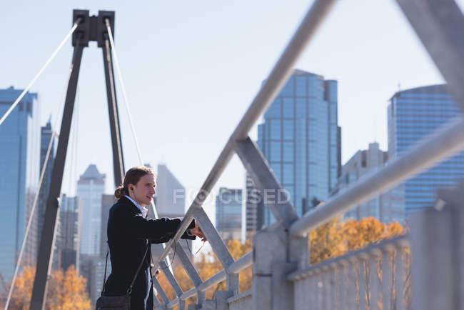 Вдумчивый человек стоит на мосту в городе — стоковое фото
