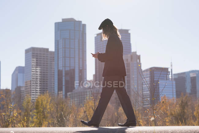 Man using mobile phone while walking on a road in the city — стоковое фото