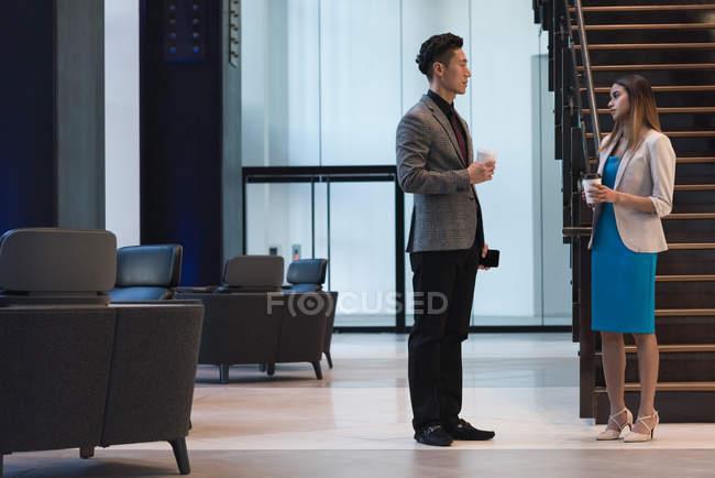 Вид сбоку деловых людей, сидящих за кофе и общающихся друг с другом в холле офиса . — стоковое фото