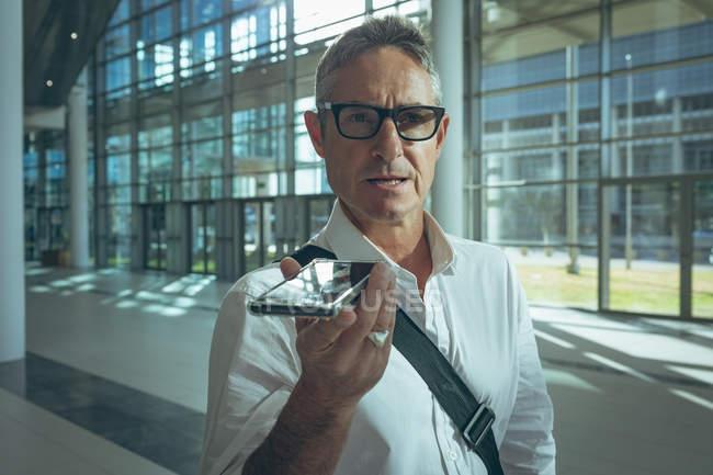 Close-up do empresário falar com o alto-falante do seu smartphone em um grande escritório — Fotografia de Stock