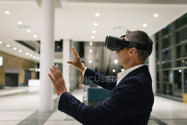 Vue latérale d'un homme d'affaires expérimentant un casque VR et levant les mains dans le couloir au bureau la nuit — Photo de stock
