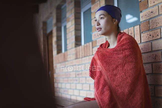 Вид сбоку молодой женщины, купающейся в ванне, сидящей возле бассейна — стоковое фото