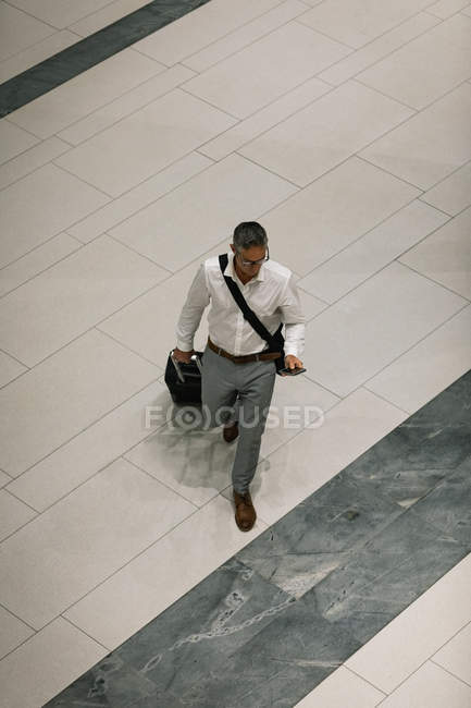 Erhabener Blick des Geschäftsmannes mit Reisekoffer auf sein Smartphone beim Gang durch den Flur — Stockfoto