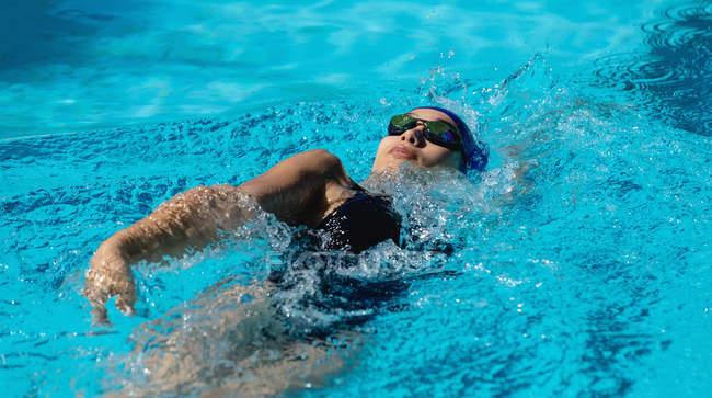 Vogelperspektive anzeigen von jungen weiblichen Schwimmer Schwimmen Rücken im Schwimmbad — Stockfoto