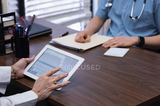 Sección media de la mujer mayor sosteniendo tableta digital en la clínica - foto de stock