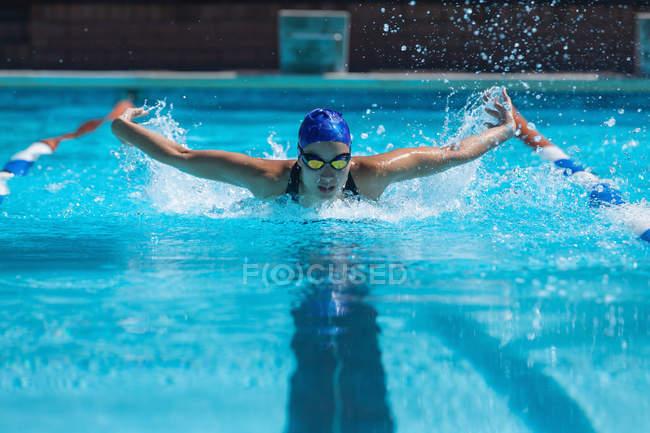 Vorderansicht des jungen weiblichen Schwimmer mit Schwimmen Goggle-Schwimmen im Schwimmbad — Stockfoto
