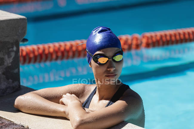 Side view of young female swimmer standing in swimming pool — Stock Photo