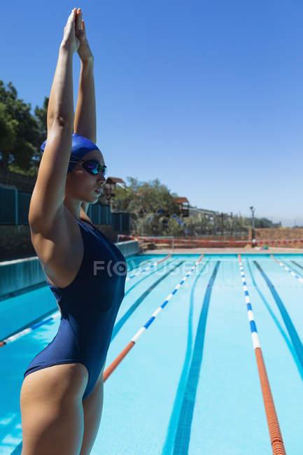 Збоку подання молодих кавказьких жіночий плавець з руки вгору і плавати окуляри готові поплавати в басейні на сонці — стокове фото