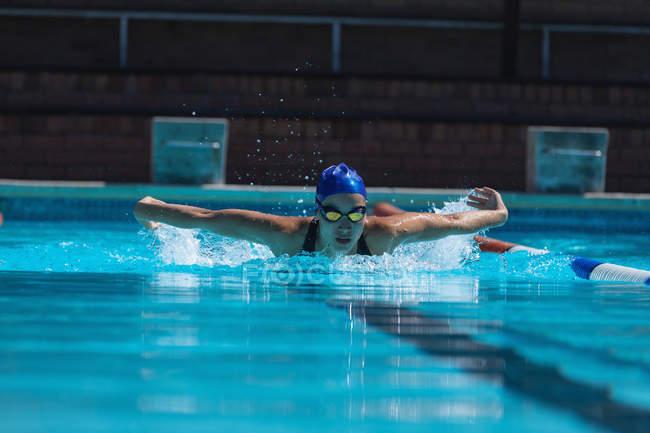 Вид спереди молодой женщины-пловчихи с плавательным аппаратом в бассейне — стоковое фото