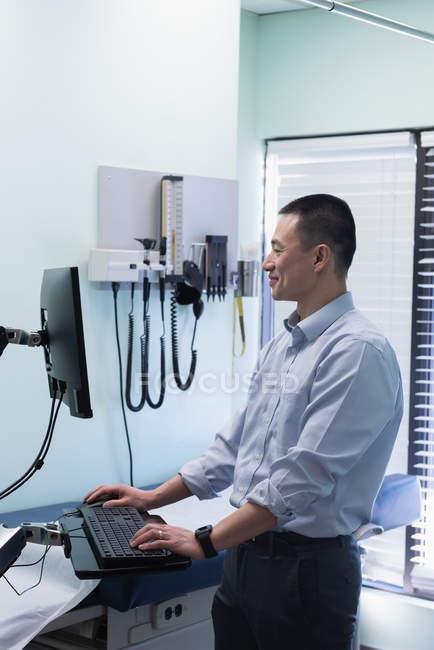 Vista lateral do jovem médico masculino asiático trabalhando no computador na clínica — Fotografia de Stock