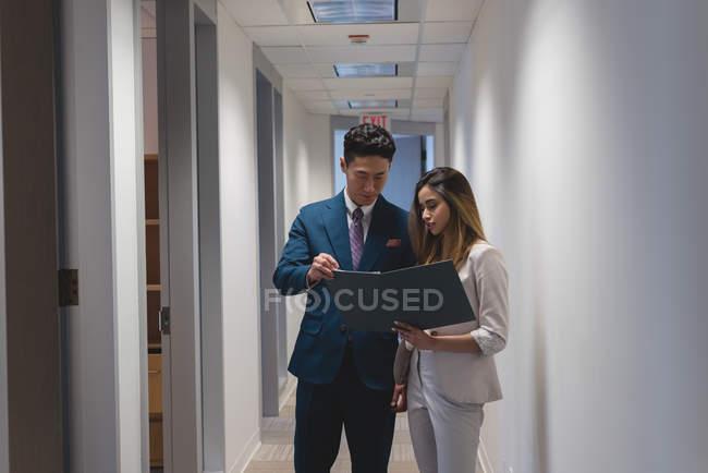 Vue du côté des hommes d'affaires, discutant un fichier dans le bureau moderne — Photo de stock