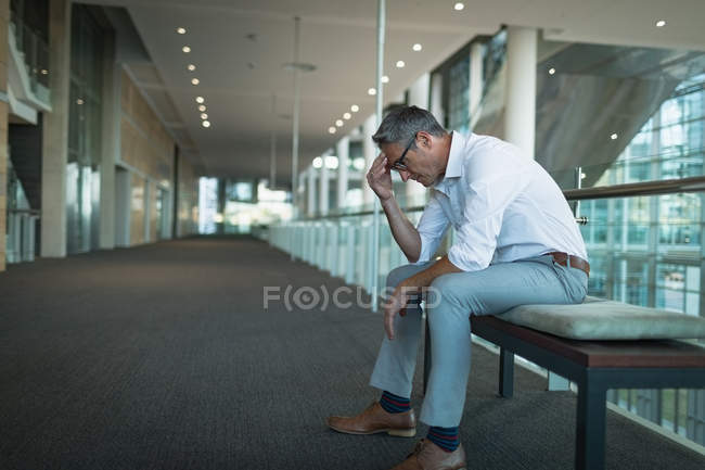 Vista lateral del frustrado hombre de negocios sentado en el banco en la oficina - foto de stock