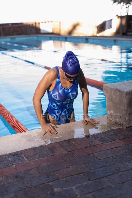 Vista frontal de la nadadora que sale de la piscina - foto de stock