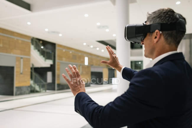 Side view of a businessman experiencing VR headset and raising his hands in the corridor in office — Stock Photo