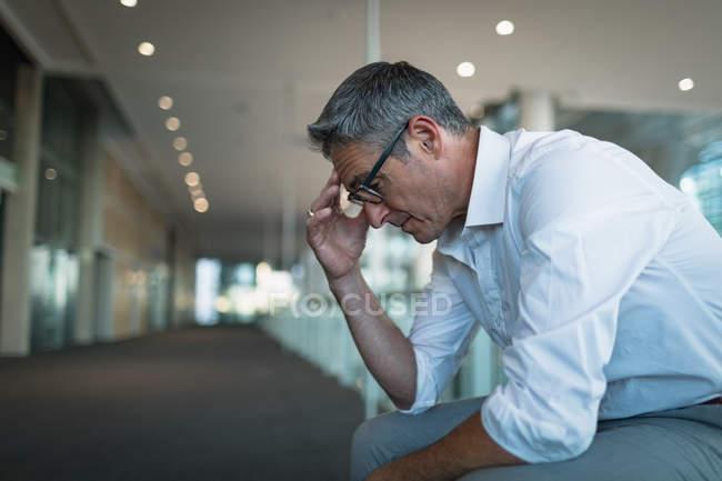Крупным планом разочарование бизнесмена, сидя в коридоре офиса — стоковое фото