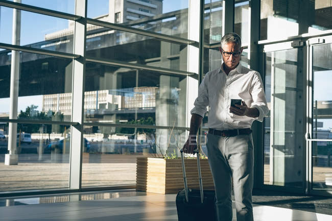 Front view of a businessman holding a travel bag while checking his mobile phone in the office — Stock Photo