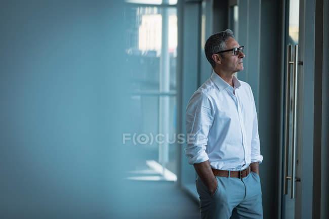 Вид збоку вдумливі бізнесмен, що дивиться крізь скло в офісі — стокове фото