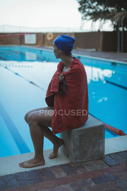 Side view of young female swimmer wrapped in towel sitting near swimming pool — Stock Photo