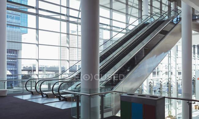 Vista lateral de cuatro escaleras mecánicas dentro de un edificio moderno con un fondo de ciudad - foto de stock