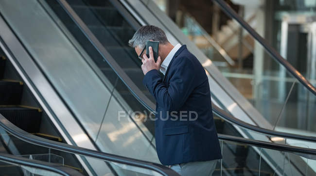 Vista lateral del hombre de negocios hablando en el teléfono móvil en la escalera mecánica en la oficina - foto de stock