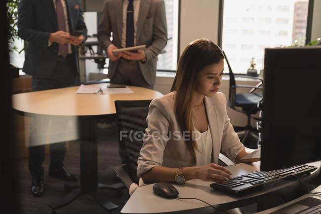 Vue latérale de la femme d'affaires travaillant sur ordinateur au bureau avec des hommes d'affaires debout en arrière-plan — Photo de stock