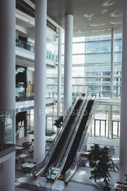 Vista elevada de escaleras mecánicas y amplia zona vacía dentro de una oficina moderna con una fondo de construcción de la ciudad - foto de stock