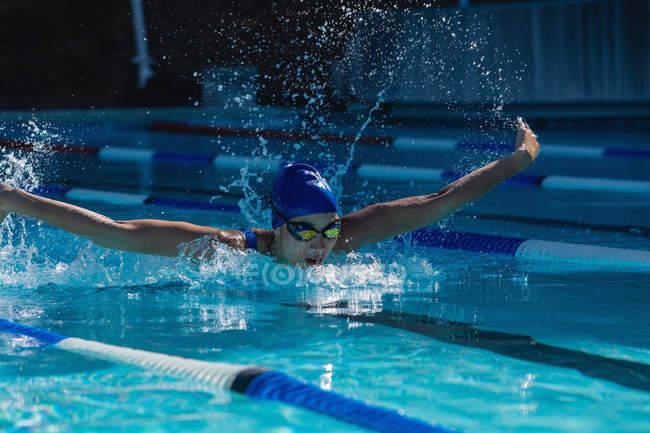 Вид спереди молодой женщины-пловца, плавающей бабочкой в бассейне в солнечный день — стоковое фото