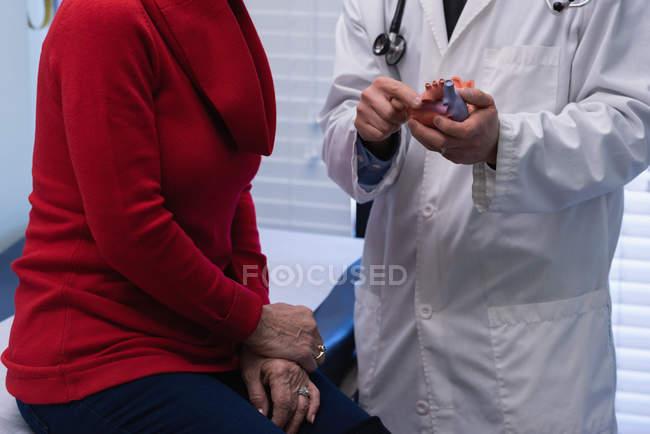 Секция MId молодого азиатского врача-мужчины и пожилого пациента обсуждает модель сердца в клинике — стоковое фото