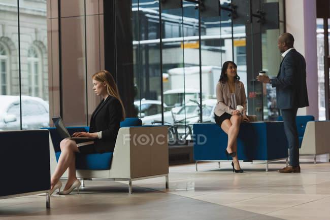 Дальний взгляд на деловую женщину с помощью ноутбука в то время как коллеги взаимодействуют друг с другом в холле в офисе — стоковое фото