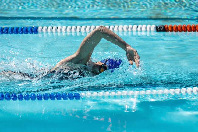 Вид сбоку молодой женщины, плавающей в бассейне в солнечный день — стоковое фото