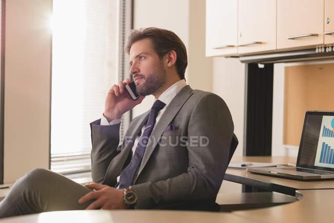 Vue latérale de l'homme d'affaires, parler au téléphone portable dans le bureau moderne — Photo de stock