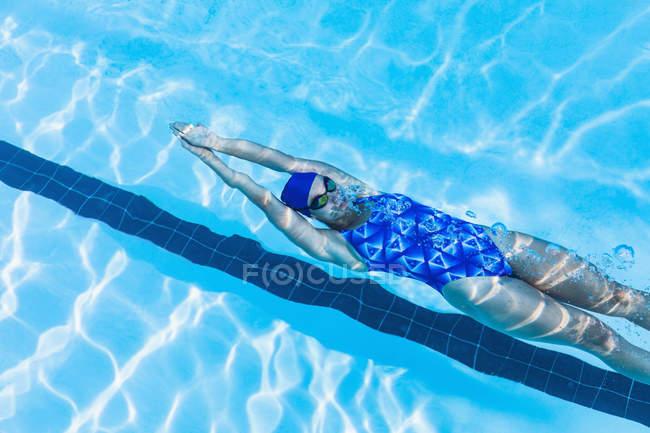 Vista de alto ângulo do nadador feminino nadando costas na piscina — Fotografia de Stock
