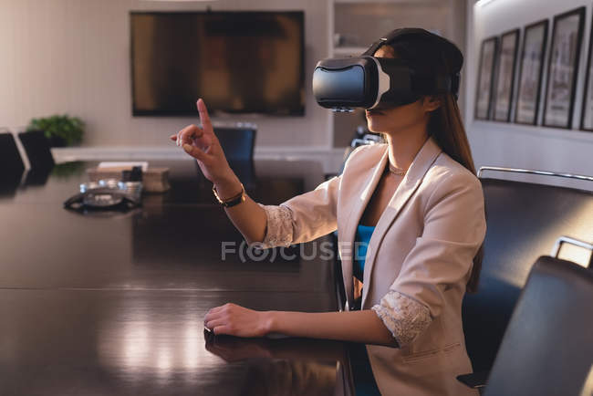 Side view of businesswoman using VR headset in the conference room at office — Stock Photo