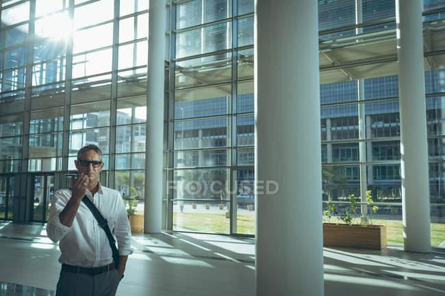 Vista frontal de un empresario hablando con el altavoz de su teléfono inteligente en la oficina de contra luz del sol - foto de stock