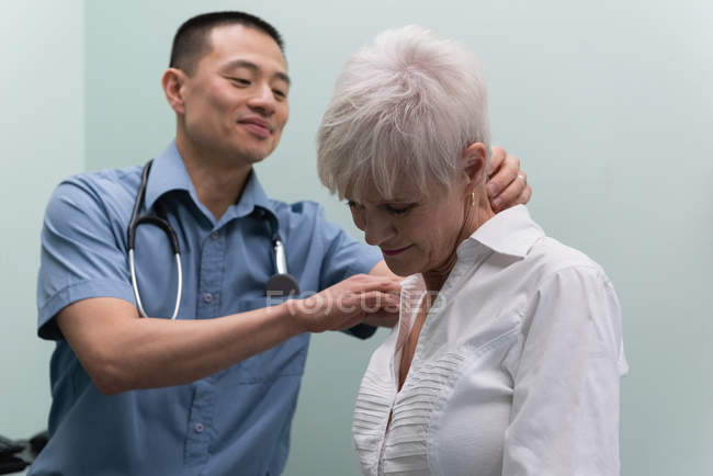 Close up of young Asian male doctor examining a senior patient in the clinic — Stock Photo
