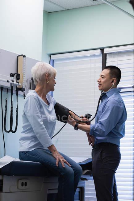 Seitenansicht eines männlichen Arztes, der den Blutdruck eines älteren Patienten in der Klinik überprüft — Stockfoto