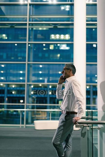 Seitenansicht eines Geschäftsmannes, der nachts vor einem Bürogebäude telefoniert — Stockfoto