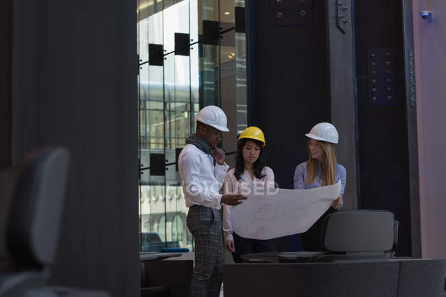 Side view of group of architects discussing over blueprint in the modern office. They are equipped with safety helmets — Stock Photo