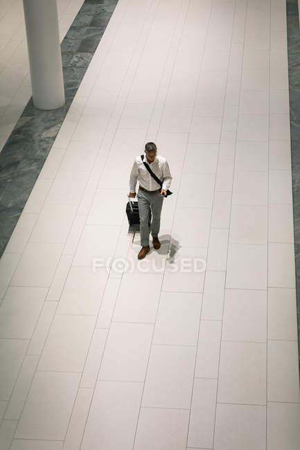 Erhabener Blick des Geschäftsmannes mit Reisekoffer, der auf sein Handy schaut, während er auf dem Flur geht — Stockfoto