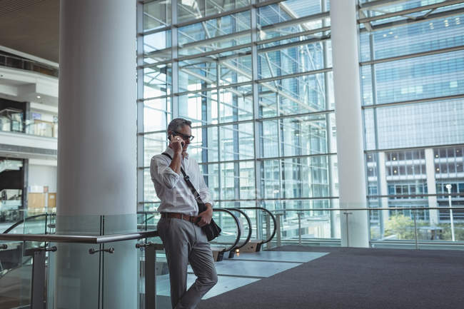 Side view of a businessman talking on the mobile phone in an empty modern office with a building background — Stock Photo