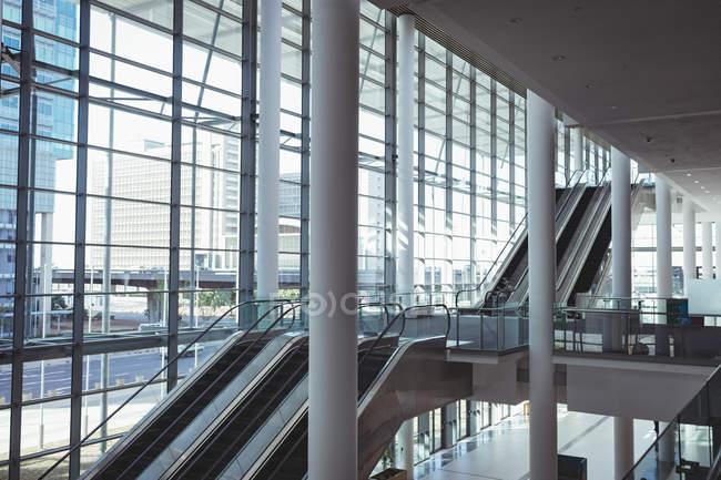 Вид збоку порожні-сучасних будівель області з ескалаторами, колони і зовнішні скляною стіною з фоном міста — стокове фото