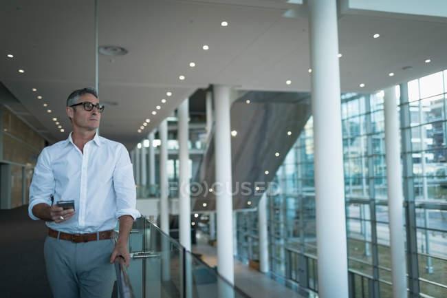 Фронтальний вид вдумливі бізнесмен з мобільного телефону фотографіях хтось дивитися вбік в офісі — стокове фото