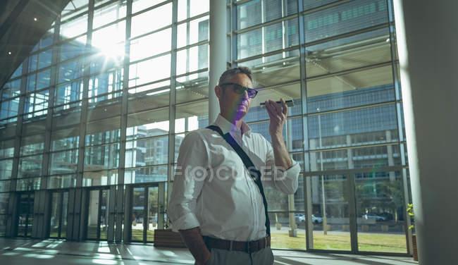 Vista lateral de um empresário escutando o alto-falante do seu smartphone no escritório contra a luz do sol — Fotografia de Stock