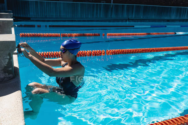 Side view of young female swimmer swimming in swimming pool — Stock Photo