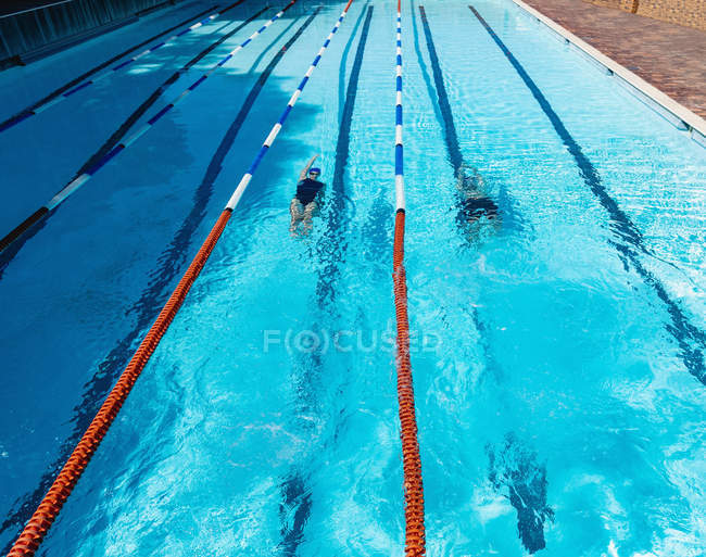 High view of young male and female swimmer swimming backstroke underwater in swimming pool — Stock Photo