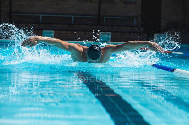 Vue de face d'un nageur mâle avec masque de natation nageant le papillon à la piscine — Photo de stock